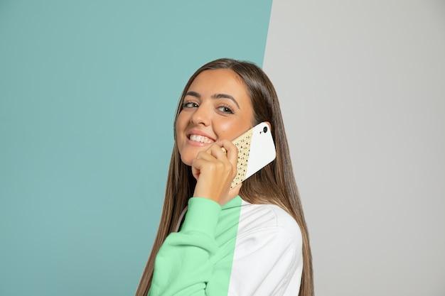 Vista laterale della donna in felpa con cappuccio che parla sullo smartphone