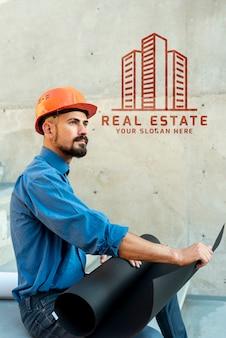 新しい建物の計画を保持している横のエージェント男