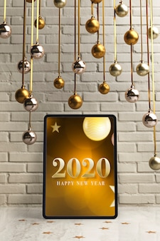 Silver and golden hanging globes on top of tablet