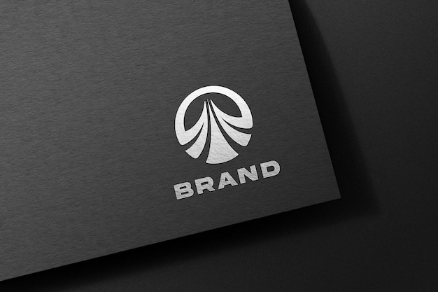 黒い紙にエンボス加工されたシルバーのロゴのモックアップ