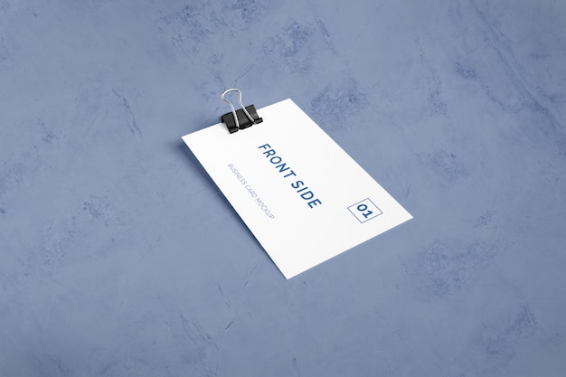 Single business card laying on marble with paper clip mockup
