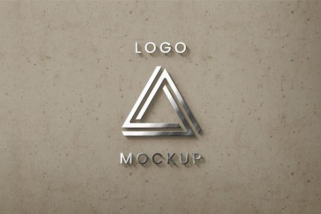 ベージュの壁のモックアップにシルバーのロゴ