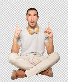 그의 손가락으로 가리키는 앉아 젊은 남자