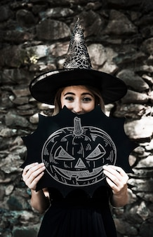 Sketch of a carved pumpkin and woman dressed as a witch