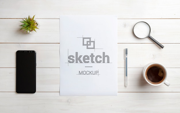Sketch mockup on blank paper. top view scene of work desk. smart phone beside. mobile app, user interface design concept