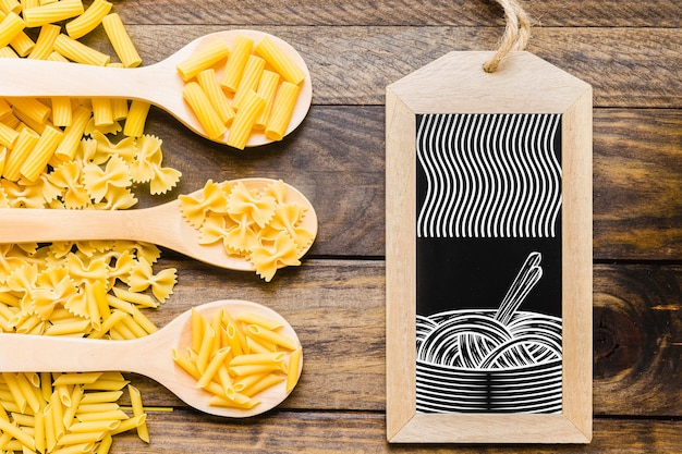 Slate mockup with pasta concept on wooden spoons Free Psd