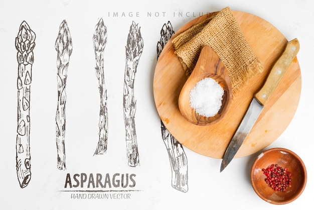 Небольшие деревянные миски с натуральной солью и красным перцем чили на деревянной разделочной доске и ножом для приготовления домашних свежих продуктов на светло-серой мраморной поверхности.