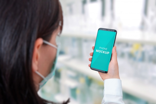 Smart phone mockup in specialist hand. hospital laboratory in background