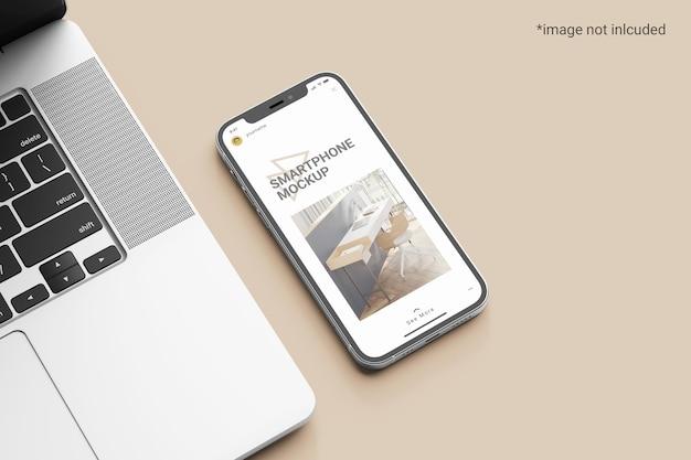 ノートパソコンの横にあるスマートフォンの画面のモックアップ
