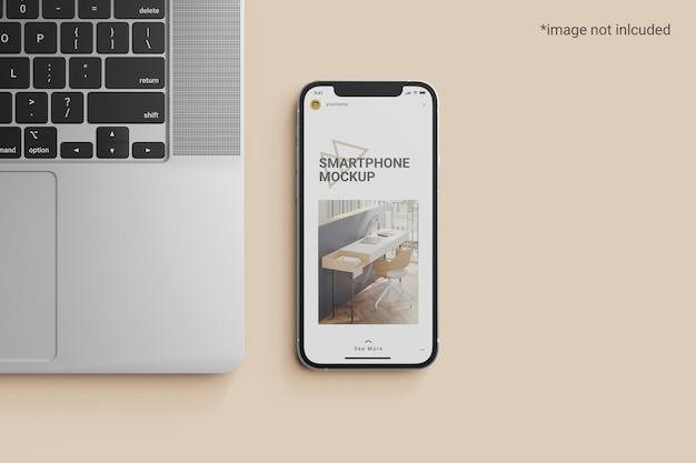 Мокап экрана смартфона рядом с ноутбуком