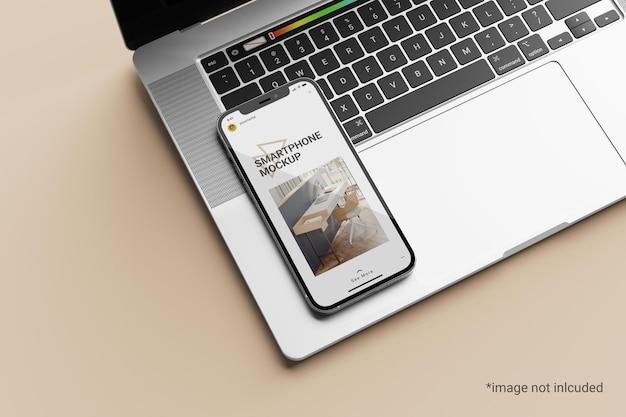 ノートパソコンの上にスマートフォンの画面のモックアップ
