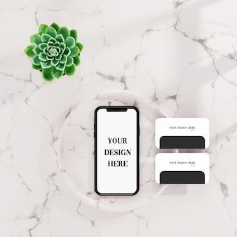 Смартфон и макет визитки на белой плитке