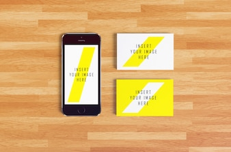 Smartphone and business card on wooden background mock up