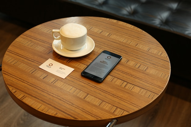 Smartphone and business card mockups psd on round table at caffee