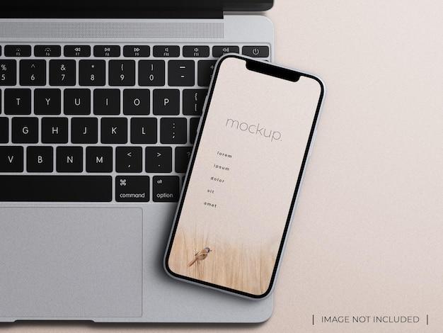 노트북 키보드 사무실 개념 평면에 스마트폰 장치 앱 화면 모형 프레젠테이션이 격리되어 있습니다.