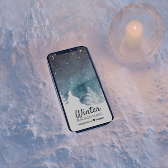 Smartphone on ice block light by candle