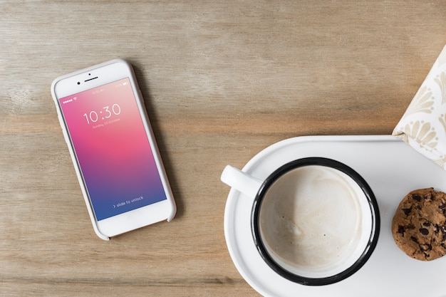 Smartphone mockup next to coffee