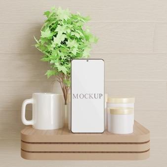 瓶とマグカップの木製の机の上に立っているスマートフォンモックアップ