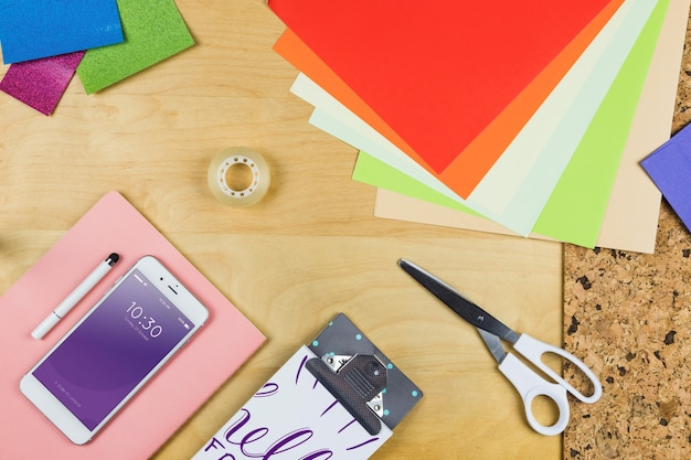 Смартфон макет с офисными материалами на столе