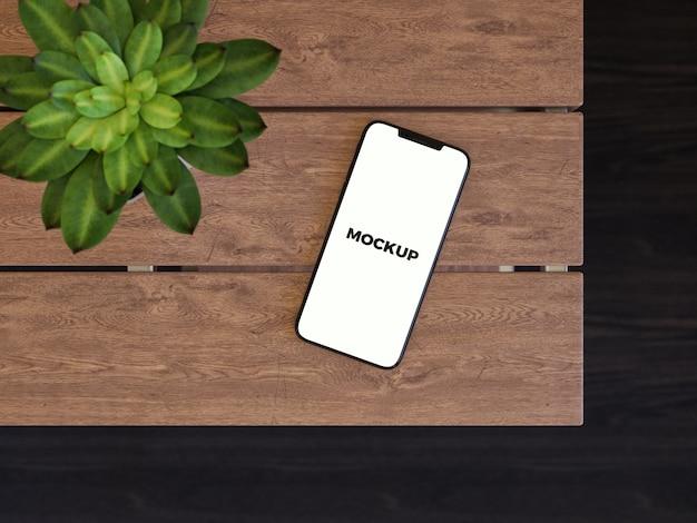 Смартфон на деревянном столе макет