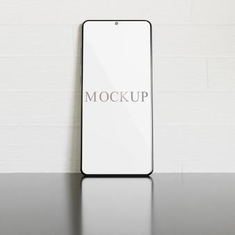 光沢のある灰色の表面にスマートフォンの画面のモックアップ