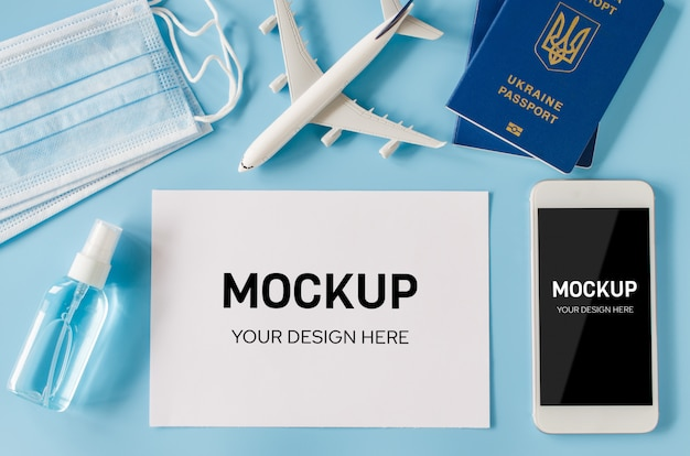 Смартфон с моделью самолета, паспортами, маской и дезинфицирующим средством