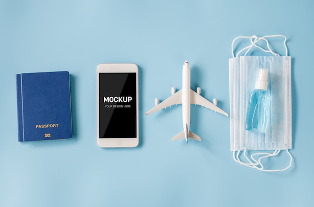 Smartphone with airplane model, passports, face mask and sanitizer