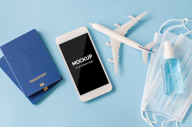 Smartphone with airplane model, passports, face mask and sanitizer.