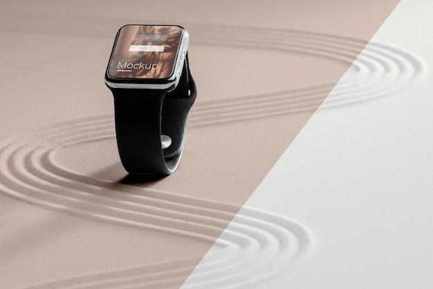 Mock-up del display dello smartwatch nella sabbia