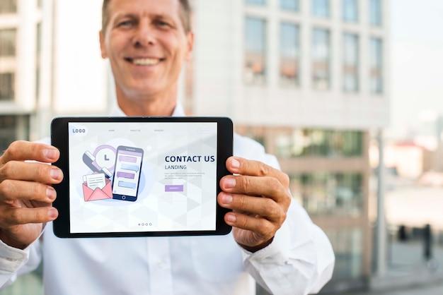 Smiley businessman outdoors holding horizontal digital tablet