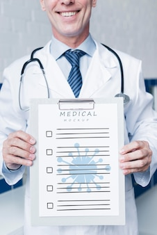 Доктор смайлик держит макет медицинской бумаги