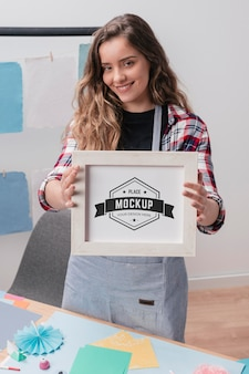 Smiley female artist holding mock-up frame