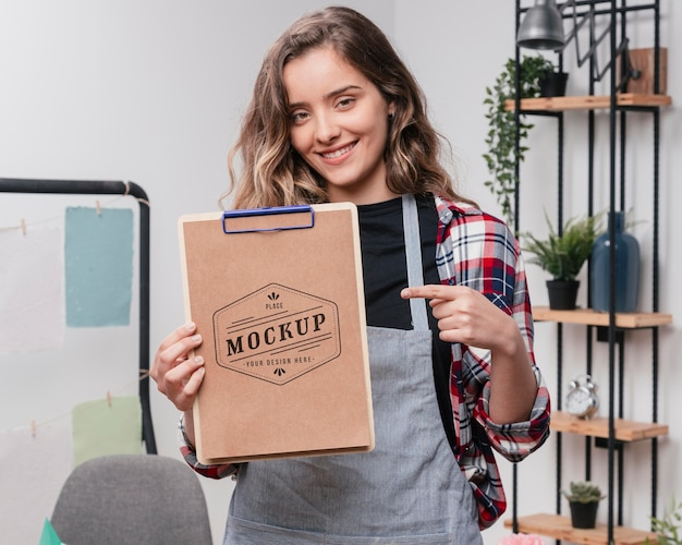 Smiley female artist holding mock-up notepad and pointing at it