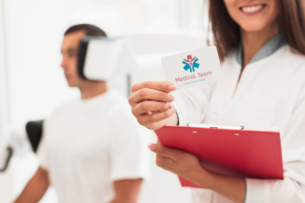Smiley female doctor holding mock-up clinical card