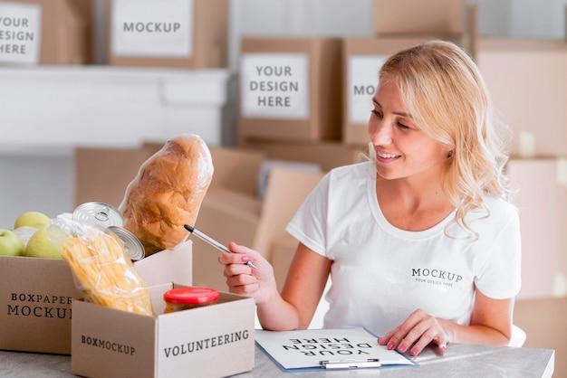 Volontario femminile di smiley che conta il cibo per le scatole di donazione