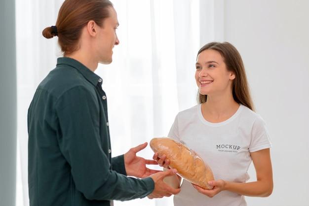 Смайлик женщина-волонтер раздает хлеб мужчине