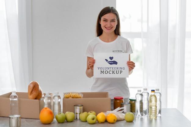 Volontario femminile smiley che tiene una pagina vuota mentre prepara il cibo per la donazione