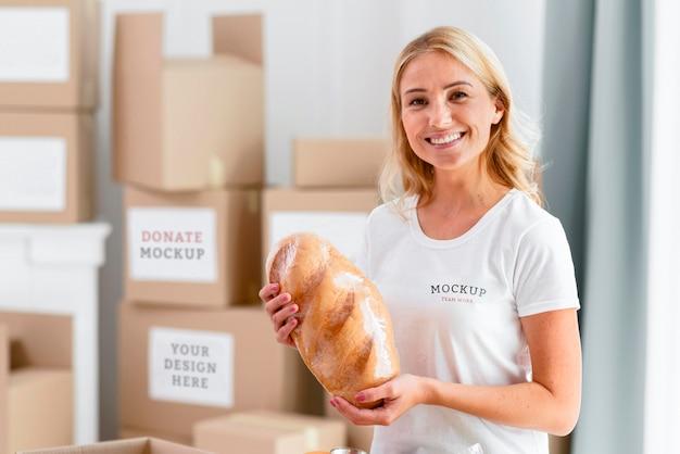Смайлик-волонтер женщина держит хлеб для пожертвования