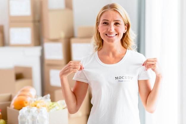 Смайлик-волонтер женщина держит ее футболку