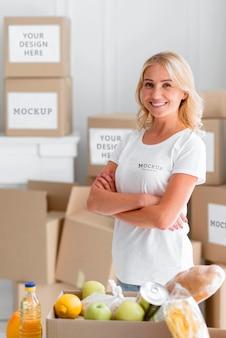 Volontario femminile di smiley in posa accanto alla scatola di cibo