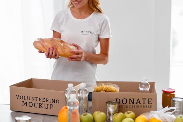 Volontario femminile di smiley che prepara il cibo nella casella per la donazione