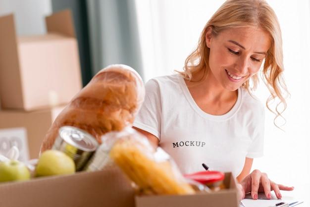 Смайлик-волонтер-женщина записывает еду для ящиков для пожертвований