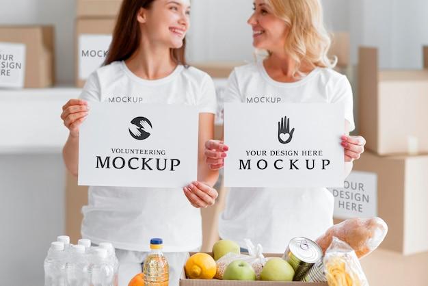 Volontari femminili di smiley che tengono documenti in bianco accanto alla scatola di cibo