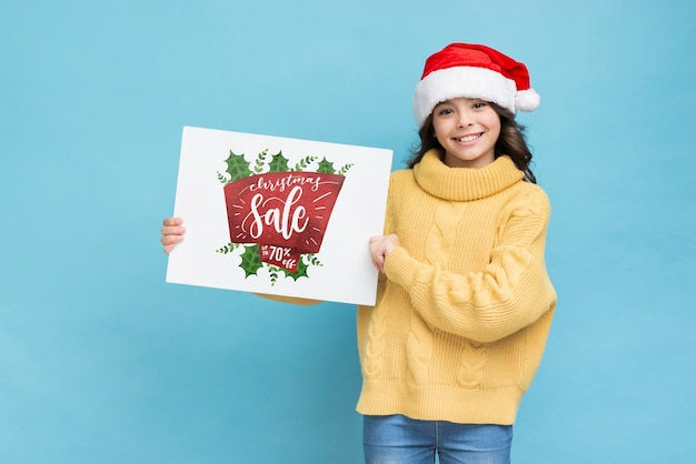 Smiley girl holding paper sheet with sales message
