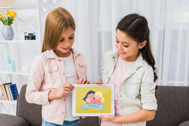 Улыбающиеся девушки держат макет планшета