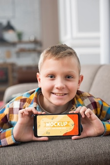 Smiley kid on couch holding smartphone