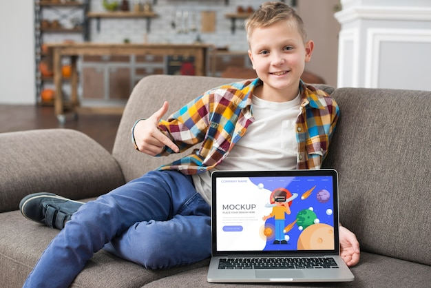 Smiley kid on couch pointing at laptop