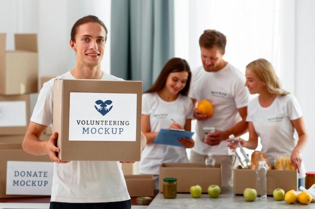 Смайлик-волонтер-мужчина держит коробку с пожертвованиями