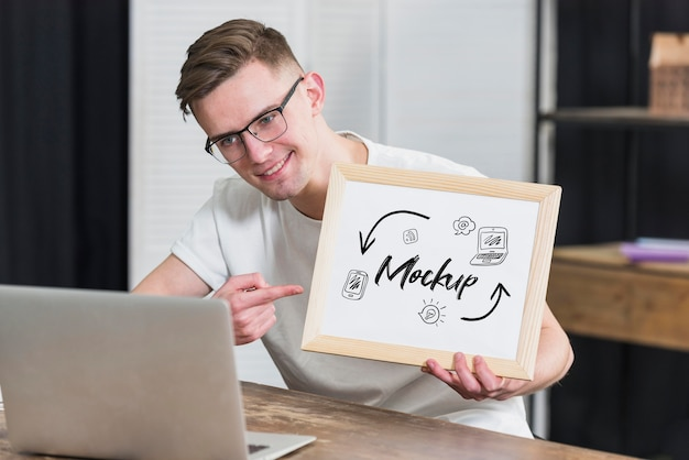 Smiley man holding mock-up frame with open laptop