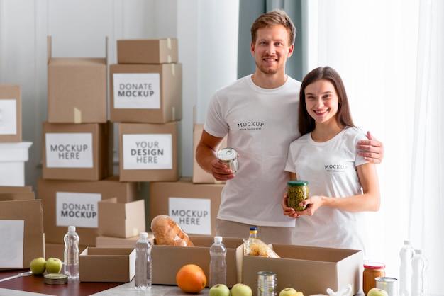 Volontari di smiley in posa insieme mentre preparano scatole di provviste per le donazioni